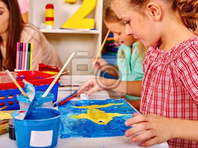 Группа маленькая девочка и женщина с малярной кистью на столе в школе. Коробка рисунок на переднем плане. Учитель помогает детям нарисовать картину., 27x20 см, на бумагеДетский сад<br>Постер на холсте или бумаге. Любого нужного вам размера. В раме или без. Подвес в комплекте. Трехслойная надежная упаковка. Доставим в любую точку России. Вам осталось только повесить картину на стену!<br>