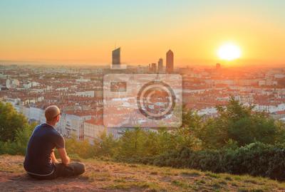 Постер Утро Человек, сидя на траве и наслаждаясь восходом солнца над городом Лион, Франция.Утро<br>Постер на холсте или бумаге. Любого нужного вам размера. В раме или без. Подвес в комплекте. Трехслойная надежная упаковка. Доставим в любую точку России. Вам осталось только повесить картину на стену!<br>