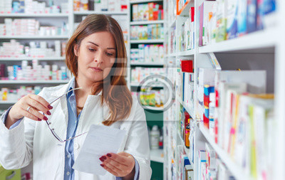 Женщина фармацевт проведения рецепт проверки лекарств в аптеке - аптека., 32x20 см, на бумагеАптека<br>Постер на холсте или бумаге. Любого нужного вам размера. В раме или без. Подвес в комплекте. Трехслойная надежная упаковка. Доставим в любую точку России. Вам осталось только повесить картину на стену!<br>