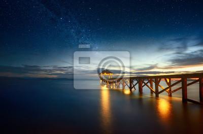 Постер Ночь Красивый ночной пейзаж с млечным путем в небе и пирсе, уходящем в океан.Ночь<br>Постер на холсте или бумаге. Любого нужного вам размера. В раме или без. Подвес в комплекте. Трехслойная надежная упаковка. Доставим в любую точку России. Вам осталось только повесить картину на стену!<br>