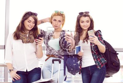 Три молодые девушки стояли с багажом в аэропорту и смотрит на телефон. Поездки с друзьями, 30x20 см, на бумагеТурфирма<br>Постер на холсте или бумаге. Любого нужного вам размера. В раме или без. Подвес в комплекте. Трехслойная надежная упаковка. Доставим в любую точку России. Вам осталось только повесить картину на стену!<br>