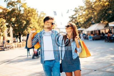 Счастливая молодая пара гуляет по городу после покупки, 30x20 см, на бумагеШоппинг<br>Постер на холсте или бумаге. Любого нужного вам размера. В раме или без. Подвес в комплекте. Трехслойная надежная упаковка. Доставим в любую точку России. Вам осталось только повесить картину на стену!<br>