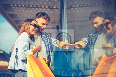 Молодая пара в торговых глядя на витрину магазина в городе, 30x20 см, на бумагеШоппинг<br>Постер на холсте или бумаге. Любого нужного вам размера. В раме или без. Подвес в комплекте. Трехслойная надежная упаковка. Доставим в любую точку России. Вам осталось только повесить картину на стену!<br>