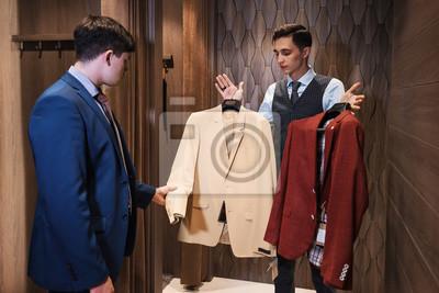 Постер Оформление офиса Консультант предлагает на выбор красный и желтый пиджак от классического костюма для бизнес-клиентов., 30x20 см, на бумагеПримерочная<br>Постер на холсте или бумаге. Любого нужного вам размера. В раме или без. Подвес в комплекте. Трехслойная надежная упаковка. Доставим в любую точку России. Вам осталось только повесить картину на стену!<br>