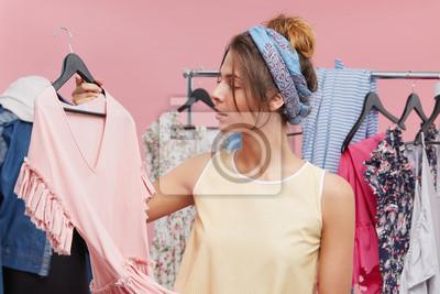 Постер Оформление офиса Молодая женщина, стоя рядом с ней шкаф, держа платье на плечики, пытаясь решить, что надеть на вечеринку. Красивая женщина, выбирая одежду или наряд в гардеробной. Люди, одежда, концепция мода, 30x20 см, на бумагеПримерочная<br>Постер на холсте или бумаге. Любого нужного вам размера. В раме или без. Подвес в комплекте. Трехслойная надежная упаковка. Доставим в любую точку России. Вам осталось только повесить картину на стену!<br>