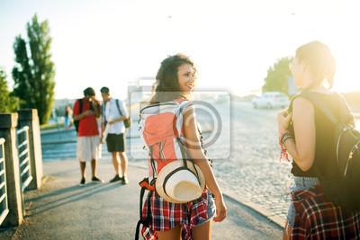 Вид сзади две красивые девушки идут по улице с рюкзаками и шляпу., 30x20 см, на бумагеТурфирма<br>Постер на холсте или бумаге. Любого нужного вам размера. В раме или без. Подвес в комплекте. Трехслойная надежная упаковка. Доставим в любую точку России. Вам осталось только повесить картину на стену!<br>