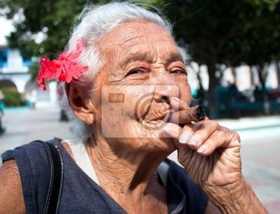 Постер Куба Морщинистая женщина с красным цветком курить сигару. КубаКуба<br>Постер на холсте или бумаге. Любого нужного вам размера. В раме или без. Подвес в комплекте. Трехслойная надежная упаковка. Доставим в любую точку России. Вам осталось только повесить картину на стену!<br>