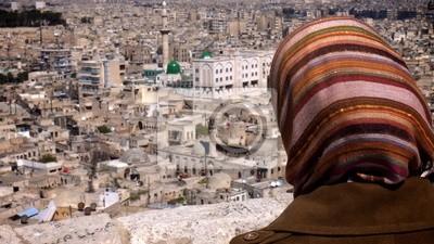 Постер Сирия Женщина в платке, глядя на АлеппоСирия<br>Постер на холсте или бумаге. Любого нужного вам размера. В раме или без. Подвес в комплекте. Трехслойная надежная упаковка. Доставим в любую точку России. Вам осталось только повесить картину на стену!<br>