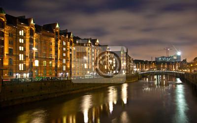 Постер Гамбург Speicherstadt на ночь в ГамбургеГамбург<br>Постер на холсте или бумаге. Любого нужного вам размера. В раме или без. Подвес в комплекте. Трехслойная надежная упаковка. Доставим в любую точку России. Вам осталось только повесить картину на стену!<br>