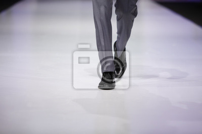 Подножия модель мужского пола в серые брюки и черные туфли на подиуме, 30x20 см, на бумагеМодели на подиуме<br>Постер на холсте или бумаге. Любого нужного вам размера. В раме или без. Подвес в комплекте. Трехслойная надежная упаковка. Доставим в любую точку России. Вам осталось только повесить картину на стену!<br>