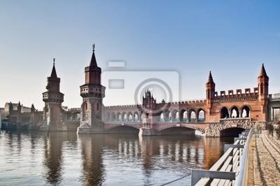 Постер Берлин В Oberbaumbrucke моста в Берлине, ГерманияБерлин<br>Постер на холсте или бумаге. Любого нужного вам размера. В раме или без. Подвес в комплекте. Трехслойная надежная упаковка. Доставим в любую точку России. Вам осталось только повесить картину на стену!<br>