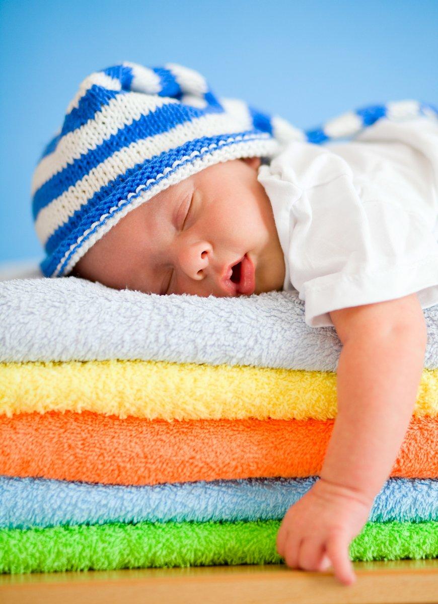 Постер Спящим младенцем на красочные полотенца стекаДети<br>Постер на холсте или бумаге. Любого нужного вам размера. В раме или без. Подвес в комплекте. Трехслойная надежная упаковка. Доставим в любую точку России. Вам осталось только повесить картину на стену!<br>