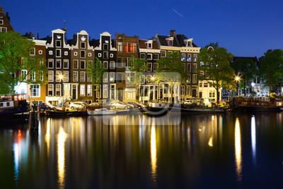 Постер Нидерланды Колоритные дома в Амстердаме в ночьНидерланды<br>Постер на холсте или бумаге. Любого нужного вам размера. В раме или без. Подвес в комплекте. Трехслойная надежная упаковка. Доставим в любую точку России. Вам осталось только повесить картину на стену!<br>