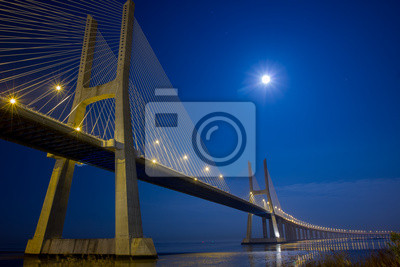 Постер Лиссабон Подвесной мост под лунным светом ночьюЛиссабон<br>Постер на холсте или бумаге. Любого нужного вам размера. В раме или без. Подвес в комплекте. Трехслойная надежная упаковка. Доставим в любую точку России. Вам осталось только повесить картину на стену!<br>
