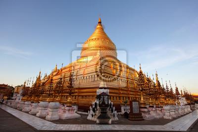 Постер Мьянма (Бирма) Shwezigon пагода в Баган, Мьянма, залитой солнцем на закатеМьянма (Бирма)<br>Постер на холсте или бумаге. Любого нужного вам размера. В раме или без. Подвес в комплекте. Трехслойная надежная упаковка. Доставим в любую точку России. Вам осталось только повесить картину на стену!<br>