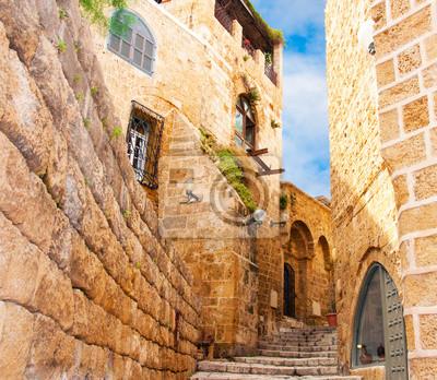 Постер Страны Узкие каменные улицы древнего Тель-Авив, Израиль, 23x20 см, на бумагеИзраиль<br>Постер на холсте или бумаге. Любого нужного вам размера. В раме или без. Подвес в комплекте. Трехслойная надежная упаковка. Доставим в любую точку России. Вам осталось только повесить картину на стену!<br>