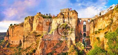 Постер Испания Панорамный вид на город Ронда на закате, Андалусия, ИспанияИспания<br>Постер на холсте или бумаге. Любого нужного вам размера. В раме или без. Подвес в комплекте. Трехслойная надежная упаковка. Доставим в любую точку России. Вам осталось только повесить картину на стену!<br>