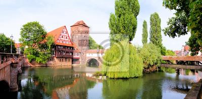 Постер Германия Панорамный вид на средневековый riverside архитектуры, НюрнбергГермания<br>Постер на холсте или бумаге. Любого нужного вам размера. В раме или без. Подвес в комплекте. Трехслойная надежная упаковка. Доставим в любую точку России. Вам осталось только повесить картину на стену!<br>