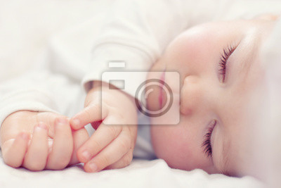 Постер Крупным планом портрет красивой спящего ребенка на беломДети<br>Постер на холсте или бумаге. Любого нужного вам размера. В раме или без. Подвес в комплекте. Трехслойная надежная упаковка. Доставим в любую точку России. Вам осталось только повесить картину на стену!<br>