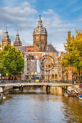 Постер Амстердам Канал и церковь Святого Николая в АмстердамеАмстердам<br>Постер на холсте или бумаге. Любого нужного вам размера. В раме или без. Подвес в комплекте. Трехслойная надежная упаковка. Доставим в любую точку России. Вам осталось только повесить картину на стену!<br>