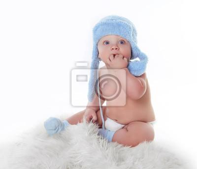 Постер Милый маленький ребенок смотрит и носить голубой шляпе с белымДети<br>Постер на холсте или бумаге. Любого нужного вам размера. В раме или без. Подвес в комплекте. Трехслойная надежная упаковка. Доставим в любую точку России. Вам осталось только повесить картину на стену!<br>