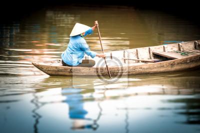 Постер Вьетнам Женщина на деревянной лодке по реке, во Вьетнаме, в Азии.Вьетнам<br>Постер на холсте или бумаге. Любого нужного вам размера. В раме или без. Подвес в комплекте. Трехслойная надежная упаковка. Доставим в любую точку России. Вам осталось только повесить картину на стену!<br>