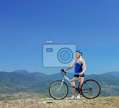 Постер Спорт Молодая женщина байкер позирует с горного велосипеда на открытом воздухе, 22x20 см, на бумагеВелосипедисты<br>Постер на холсте или бумаге. Любого нужного вам размера. В раме или без. Подвес в комплекте. Трехслойная надежная упаковка. Доставим в любую точку России. Вам осталось только повесить картину на стену!<br>