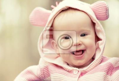 Постер Счастливой улыбкой девочка в розовом капоте с ушамиДети<br>Постер на холсте или бумаге. Любого нужного вам размера. В раме или без. Подвес в комплекте. Трехслойная надежная упаковка. Доставим в любую точку России. Вам осталось только повесить картину на стену!<br>