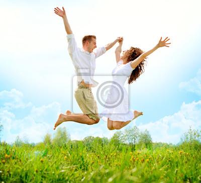 Постер Счастливая Пара На Открытом Воздухе. Прыжки семьи на зеленом полеЭмоции<br>Постер на холсте или бумаге. Любого нужного вам размера. В раме или без. Подвес в комплекте. Трехслойная надежная упаковка. Доставим в любую точку России. Вам осталось только повесить картину на стену!<br>