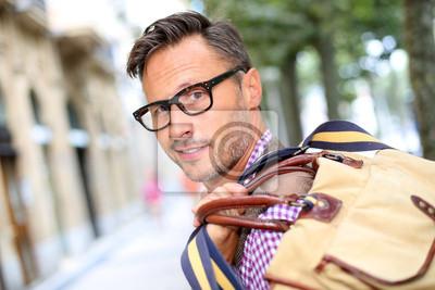 Постер Модные улыбчивый парень путешествует с мешкомМужской стиль, сумки<br>Постер на холсте или бумаге. Любого нужного вам размера. В раме или без. Подвес в комплекте. Трехслойная надежная упаковка. Доставим в любую точку России. Вам осталось только повесить картину на стену!<br>