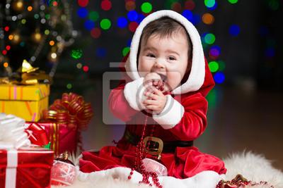 Постер Ребенок девочка в костюме Санта Клауса в рождественской елки с подаркамиДети<br>Постер на холсте или бумаге. Любого нужного вам размера. В раме или без. Подвес в комплекте. Трехслойная надежная упаковка. Доставим в любую точку России. Вам осталось только повесить картину на стену!<br>