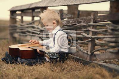 Постер Симпатичный мальчик с гитарой на местеДети<br>Постер на холсте или бумаге. Любого нужного вам размера. В раме или без. Подвес в комплекте. Трехслойная надежная упаковка. Доставим в любую точку России. Вам осталось только повесить картину на стену!<br>