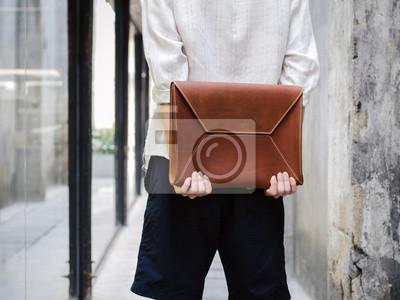 Постер Человек с кожаным мешкомМужской стиль, сумки<br>Постер на холсте или бумаге. Любого нужного вам размера. В раме или без. Подвес в комплекте. Трехслойная надежная упаковка. Доставим в любую точку России. Вам осталось только повесить картину на стену!<br>