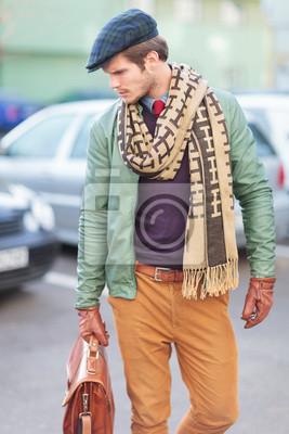 Постер Вид сбоку элегантный модный молодой человек позируетМужской стиль, сумки<br>Постер на холсте или бумаге. Любого нужного вам размера. В раме или без. Подвес в комплекте. Трехслойная надежная упаковка. Доставим в любую точку России. Вам осталось только повесить картину на стену!<br>
