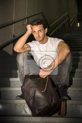 Постер Красивый молодой человек сидя на лестнице гранитные ступениМужской стиль, сумки<br>Постер на холсте или бумаге. Любого нужного вам размера. В раме или без. Подвес в комплекте. Трехслойная надежная упаковка. Доставим в любую точку России. Вам осталось только повесить картину на стену!<br>