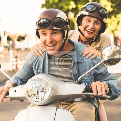 Постер-картина Фото-постеры Счастливая пожилая пара садится на скутер в городе, 20x20 см, на бумагеМотороллеры<br>Постер на холсте или бумаге. Любого нужного вам размера. В раме или без. Подвес в комплекте. Трехслойная надежная упаковка. Доставим в любую точку России. Вам осталось только повесить картину на стену!<br>