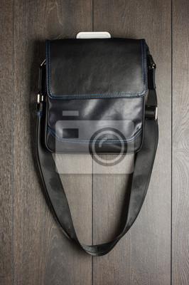 Постер Черная роскошная кожаная мужская сумочка вешается на стенуМужской стиль, сумки<br>Постер на холсте или бумаге. Любого нужного вам размера. В раме или без. Подвес в комплекте. Трехслойная надежная упаковка. Доставим в любую точку России. Вам осталось только повесить картину на стену!<br>
