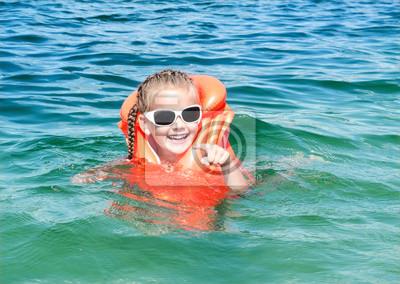 Постер Безопасность жизнедеятельности Улыбаясь маленькая девочка с купания спасательный жилетБезопасность жизнедеятельности<br>Постер на холсте или бумаге. Любого нужного вам размера. В раме или без. Подвес в комплекте. Трехслойная надежная упаковка. Доставим в любую точку России. Вам осталось только повесить картину на стену!<br>