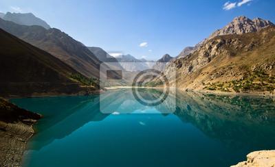 Постер Фанские горы Голубое горное озеро отражает высокие скалыФанские горы<br>Постер на холсте или бумаге. Любого нужного вам размера. В раме или без. Подвес в комплекте. Трехслойная надежная упаковка. Доставим в любую точку России. Вам осталось только повесить картину на стену!<br>