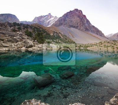 Постер Фанские горы Глубокое синее озеро в Фанских горах на рассветеФанские горы<br>Постер на холсте или бумаге. Любого нужного вам размера. В раме или без. Подвес в комплекте. Трехслойная надежная упаковка. Доставим в любую точку России. Вам осталось только повесить картину на стену!<br>
