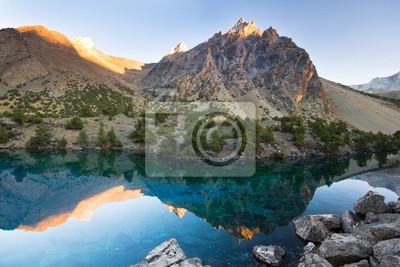 Постер Фанские горы Голубое горное озеро на закатеФанские горы<br>Постер на холсте или бумаге. Любого нужного вам размера. В раме или без. Подвес в комплекте. Трехслойная надежная упаковка. Доставим в любую точку России. Вам осталось только повесить картину на стену!<br>