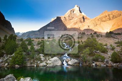 Постер Фанские горы Глубокое синее озеро в горах на рассветеФанские горы<br>Постер на холсте или бумаге. Любого нужного вам размера. В раме или без. Подвес в комплекте. Трехслойная надежная упаковка. Доставим в любую точку России. Вам осталось только повесить картину на стену!<br>