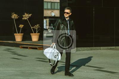 Постер Красивая мода мужской модели идут по улицеМужской стиль, сумки<br>Постер на холсте или бумаге. Любого нужного вам размера. В раме или без. Подвес в комплекте. Трехслойная надежная упаковка. Доставим в любую точку России. Вам осталось только повесить картину на стену!<br>