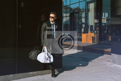 Постер Симпатичный взрослый мужчина, стоя возле черной стены и смотрит в сторонуМужской стиль, сумки<br>Постер на холсте или бумаге. Любого нужного вам размера. В раме или без. Подвес в комплекте. Трехслойная надежная упаковка. Доставим в любую точку России. Вам осталось только повесить картину на стену!<br>