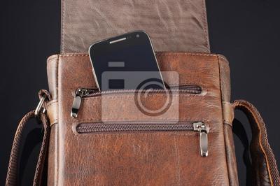 Постер Мобильный телефон в кармане кожаная сумкаМужской стиль, сумки<br>Постер на холсте или бумаге. Любого нужного вам размера. В раме или без. Подвес в комплекте. Трехслойная надежная упаковка. Доставим в любую точку России. Вам осталось только повесить картину на стену!<br>