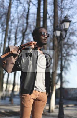 Постер Мода элегантные молодых африканских человек, одетый в черную кожаную курткуМужской стиль, сумки<br>Постер на холсте или бумаге. Любого нужного вам размера. В раме или без. Подвес в комплекте. Трехслойная надежная упаковка. Доставим в любую точку России. Вам осталось только повесить картину на стену!<br>