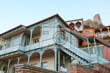 Blue carved wooden balcony under city fortress hill. Tbilisi, Old Town,
