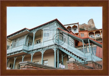 Магнитная картина Blue carved wooden balcony under city fortress hill. Tbilisi, Old Town,